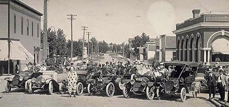 Cars, people and a clown on a Deerwood street, 1914