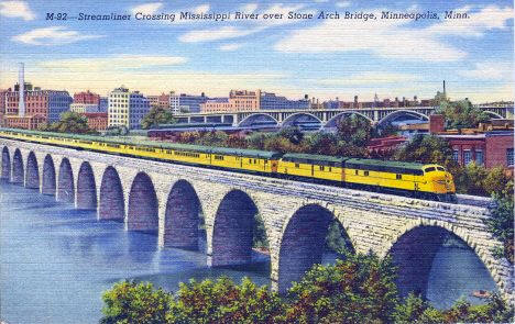 Streamliner Passenger Train crossing Mississippi River over Stone Arch Bridge in Minneapolis Minnesota, 1943