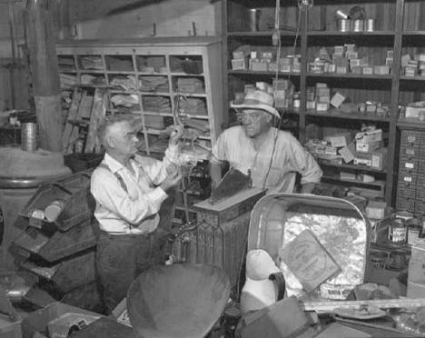Owner Robert E. Gadola with unidentified man in the Gadola Hardware Store in Ogilvie Minnesota